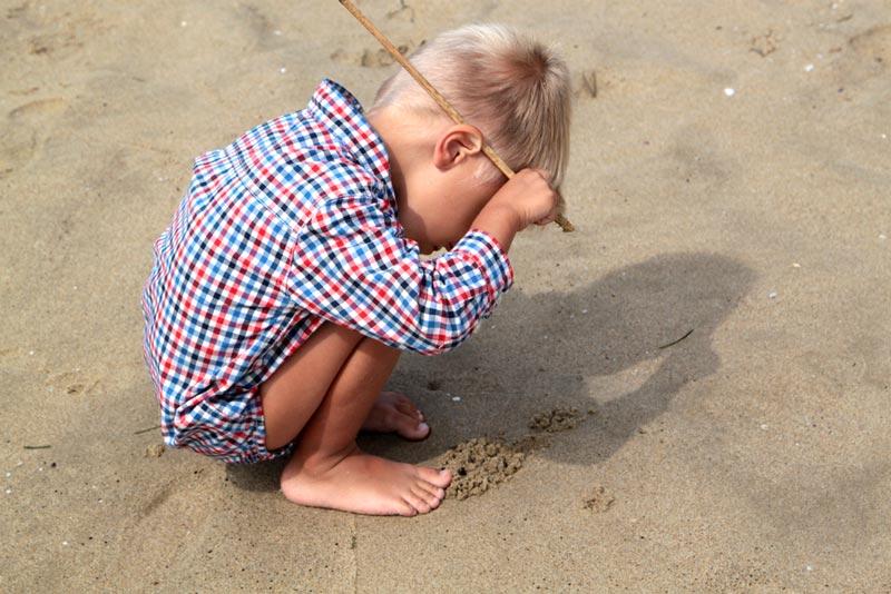 παιδί-ζωγραφίζει-στην-άμμο
